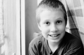 Fotografie cute ten years old autistic boy smiling and looking at camera, black and white