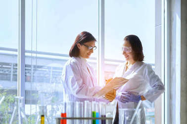 Young female scientist standing with techer in lab worker making