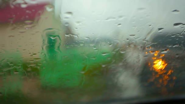 City street in the rain through wet glass