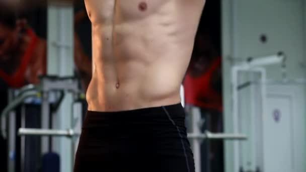 junger athletischer Mann führt Muskelübungen durch