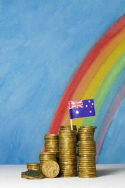 Gold Australian dollar coins against a blue sky and rainbow back