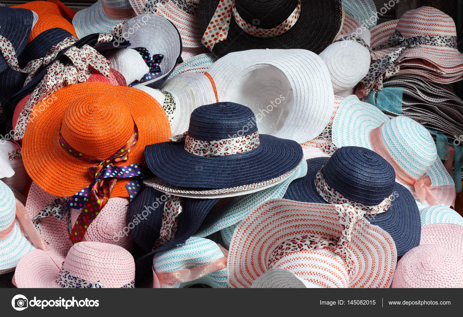 b4947ad4d5cbf Summer fashion hats piled high at an Asian outdoor market stall. — Photo by  Juan Gomez