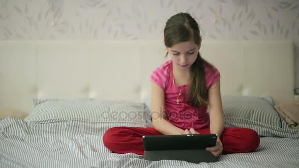 Dívka na posteli vzdělání na tabletu