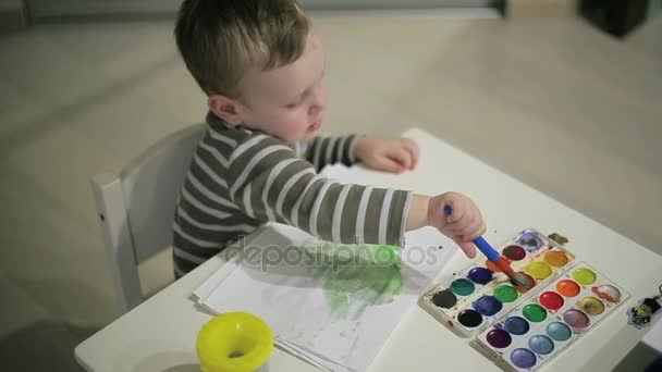 Malý kluk maluje barvy na stůl