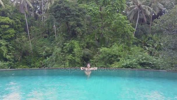 Dívka se plave v bazénu. Letecký pohled