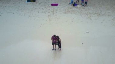 Boy and girl on the beach ocean. Aerial view. Bali