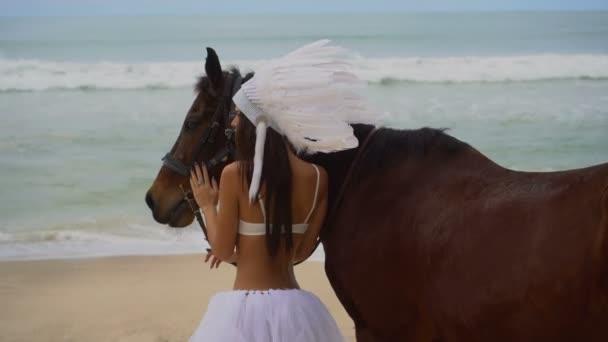 Frau mit braunem Pferd am Strand