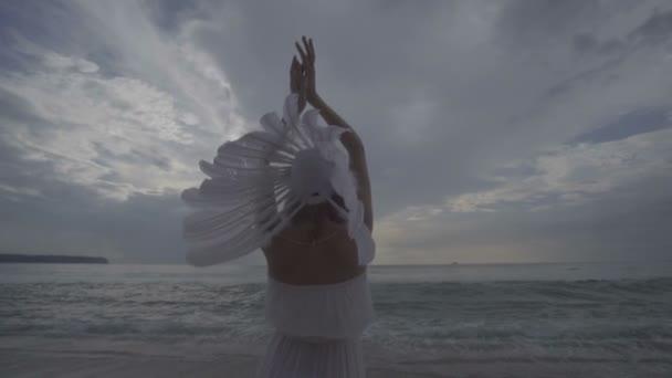 Frau mit Indianerhut mit weißer Feder am Strand