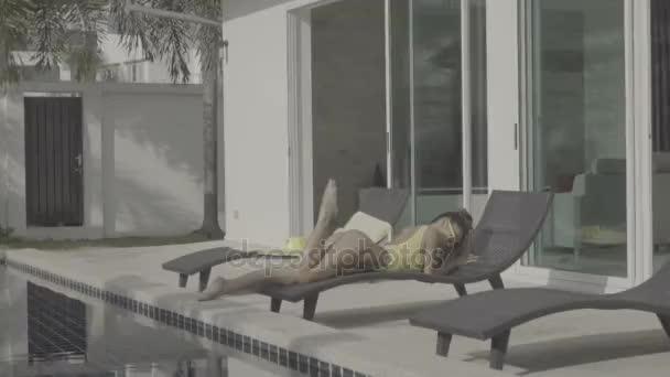 Szexi nő sárga fürdőruhát a medencénél