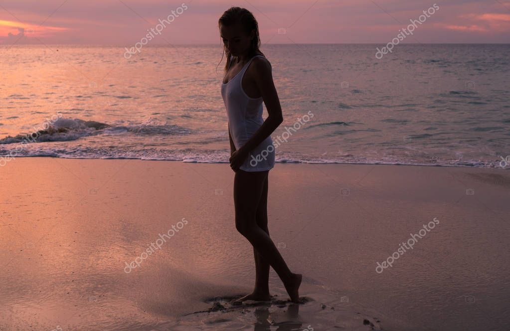Silhouette of woman  looking at the sea and sunset