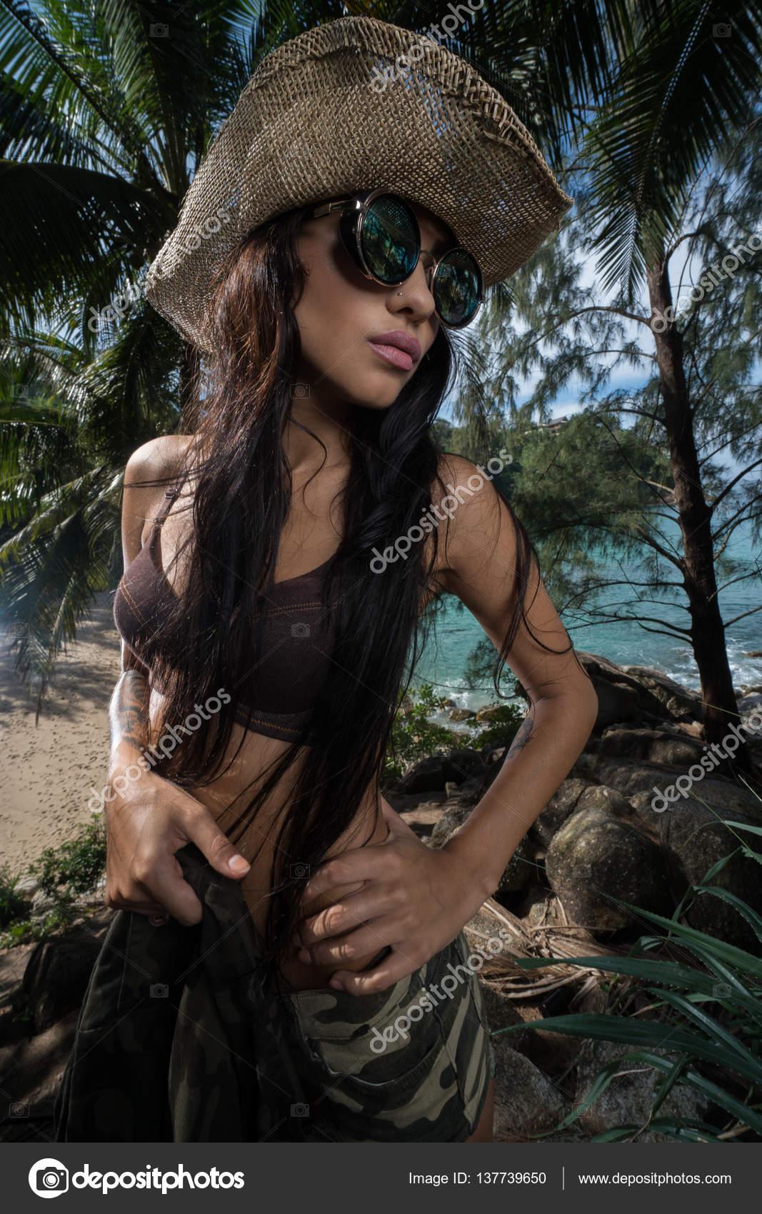 4e6bd3cc215b3c Attraente ragazza bruna in look sexy dell'esercito con cappello di paglia e  occhiali da sole in piedi nella foresta di alberi di palme tropicali sopra  la ...