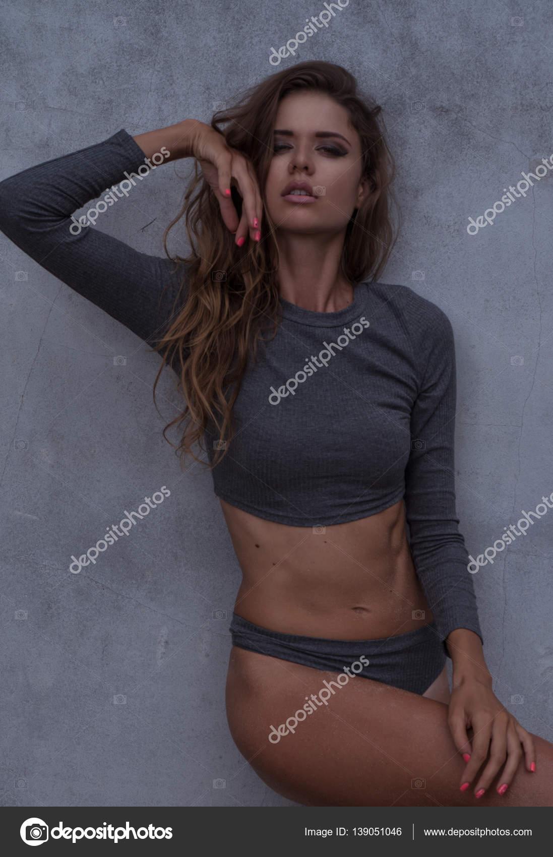 Sensuelle femme blonde portant gris manches longues combinaison bodycon en  regardant la caméra et la pose sur mur en béton — Image de nelka7812 8c24dfc2009