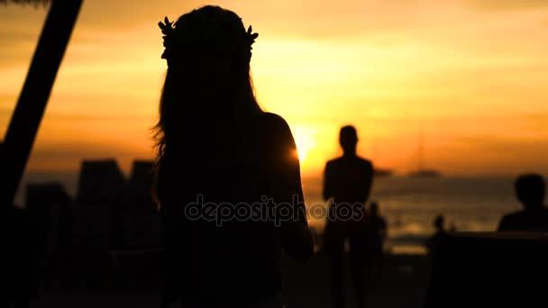 šťastná žena tančí na pláži při západu slunce s pozadím moře