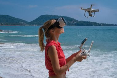 Woman with drone camera and virtual reality glasses taking photos and videos on the beach