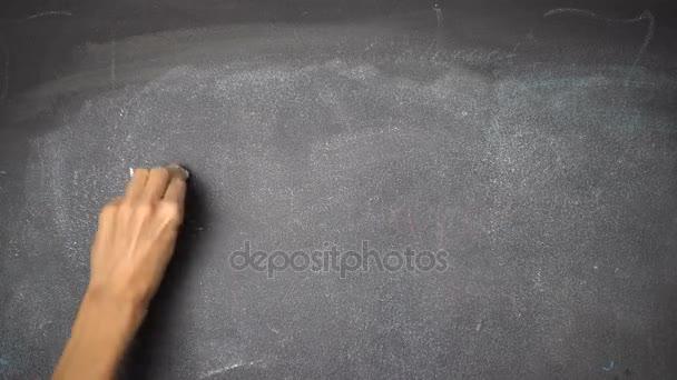 Hand writing HOME on black chalkboard
