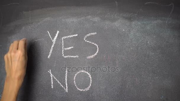 Hand writing YES, NO on black chalkboard