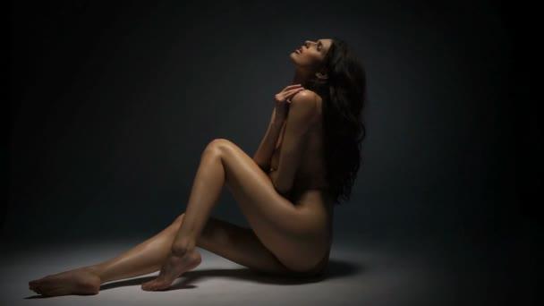 Érzéki meztelen nő sötét stúdióban