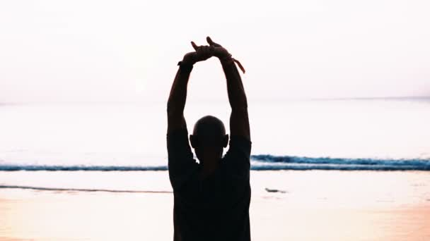 Back view of man standing on the beach with arms up in the air during beautiful sunset - video in slow motion