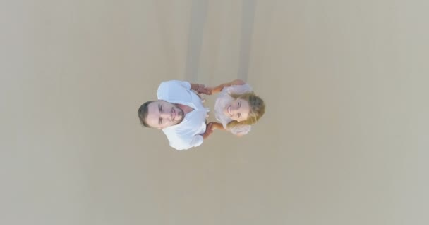Top drone view of smiling  couple on the sandy tropical beach
