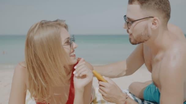 Šťastný pár použití sun opalovací mléko na pláži, člověk opalovací krém opalovací krém na ženu - video v pomalém pohybu