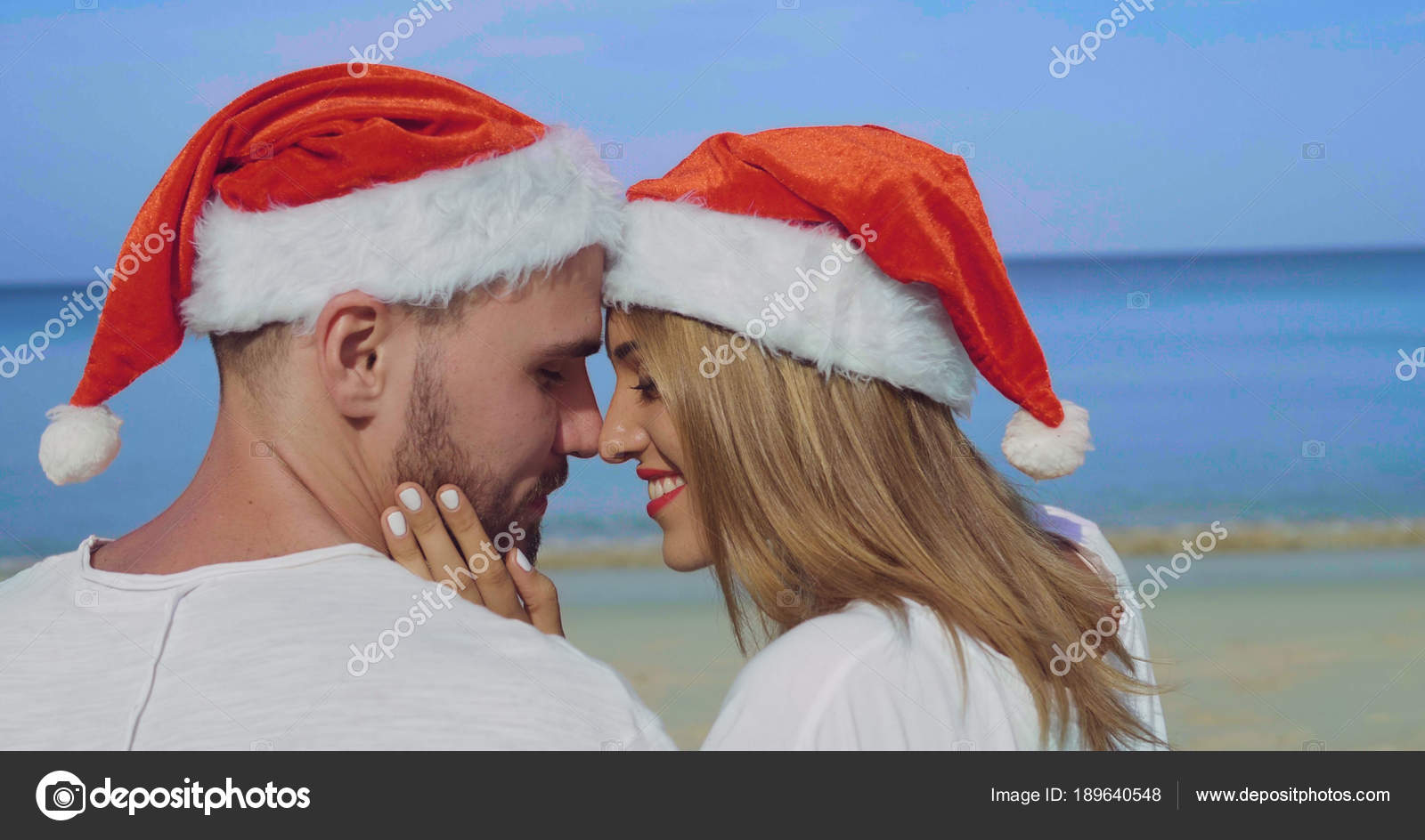 6e36749e Christmas beautiful beach couple wearing Santa hat in summer sun in love on  travel holidays on tropical travel destination during winter holidays– stock  ...
