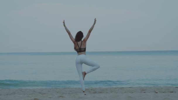 Krásná dívka cvičení na písečné pláži / krásná mladá dívka cvičení ráno na písečné pláži - video v pomalém pohybu