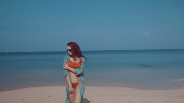 Beautiful girl on the tropical beach / Beautiful girl in bikini and colorful beach cover up relaxing in the sun during summer holiday on the tropical beach