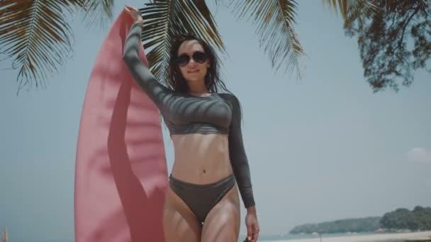 Krásná mladá dívka s Surf během letních prázdnin / krásná mladá žena v plavky a sluneční brýle pózuje s růžovou Surf během slunečného letního dne nad palm tree a obloha pozadí - video v pomalém pohybu