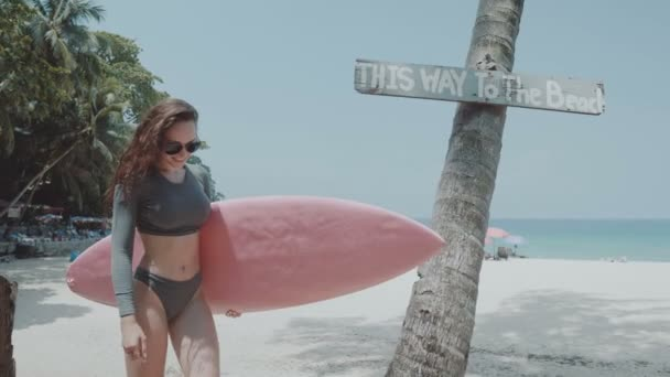 Beautiful young girl with surfboard during summer holidays / Happy young woman in swimsuit and sunglasses walking with pink surfboard during sunny summer day over palm tree and sky background - video in slow motion