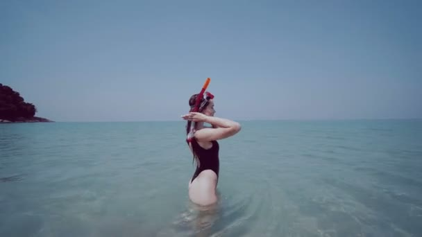 Beautiful young girl with snorkeling  mask during summer holidays / Beautiful young woman in swimsuit with snorkeling  mask having fun in the sea water, enjoying sunny summer day on her beach tropical holiday