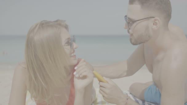 Nádherný pár během letních prázdnin / šťastný pár použití opalovací krém na opalování na pláži, člověk opalovací krém opalovací krém na ženu - video v pomalém pohybu