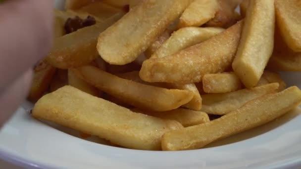 Mleté hovězí maso a fazole omáčkou na vrcholu francouzské hranolky / detailní šéfkuchaře ruční uvedení chilli con carne omáčka na vrcholu francouzské hranolky hranolky