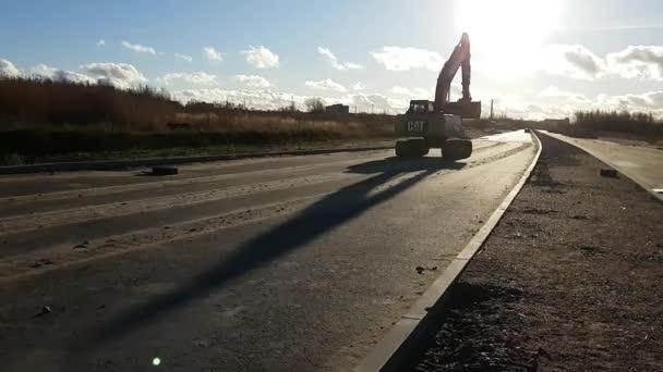 Crawler excavator with bucket on construction road