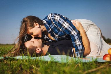 couple lie on the grass. girl top of the guy. She kisses him
