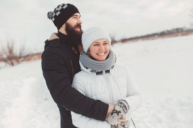 Romance couple hugging and laughing in the background of winter nature