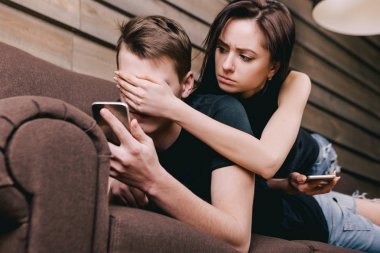 Young couple on sofa with cell phone
