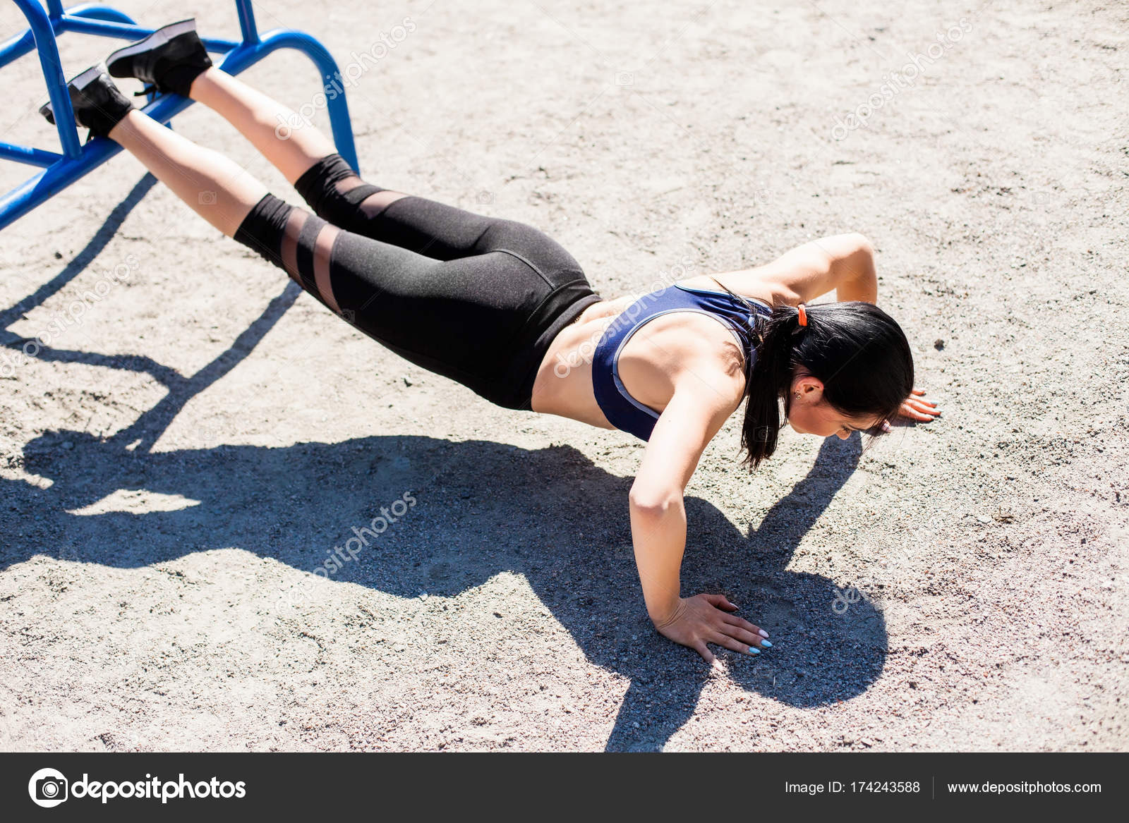 133f5eebc5056 Young sportive teenager in a bright blue sport bra and black leggings doing  push ups on the sport playground. Photo of an athlete girl with a beautiful  ...