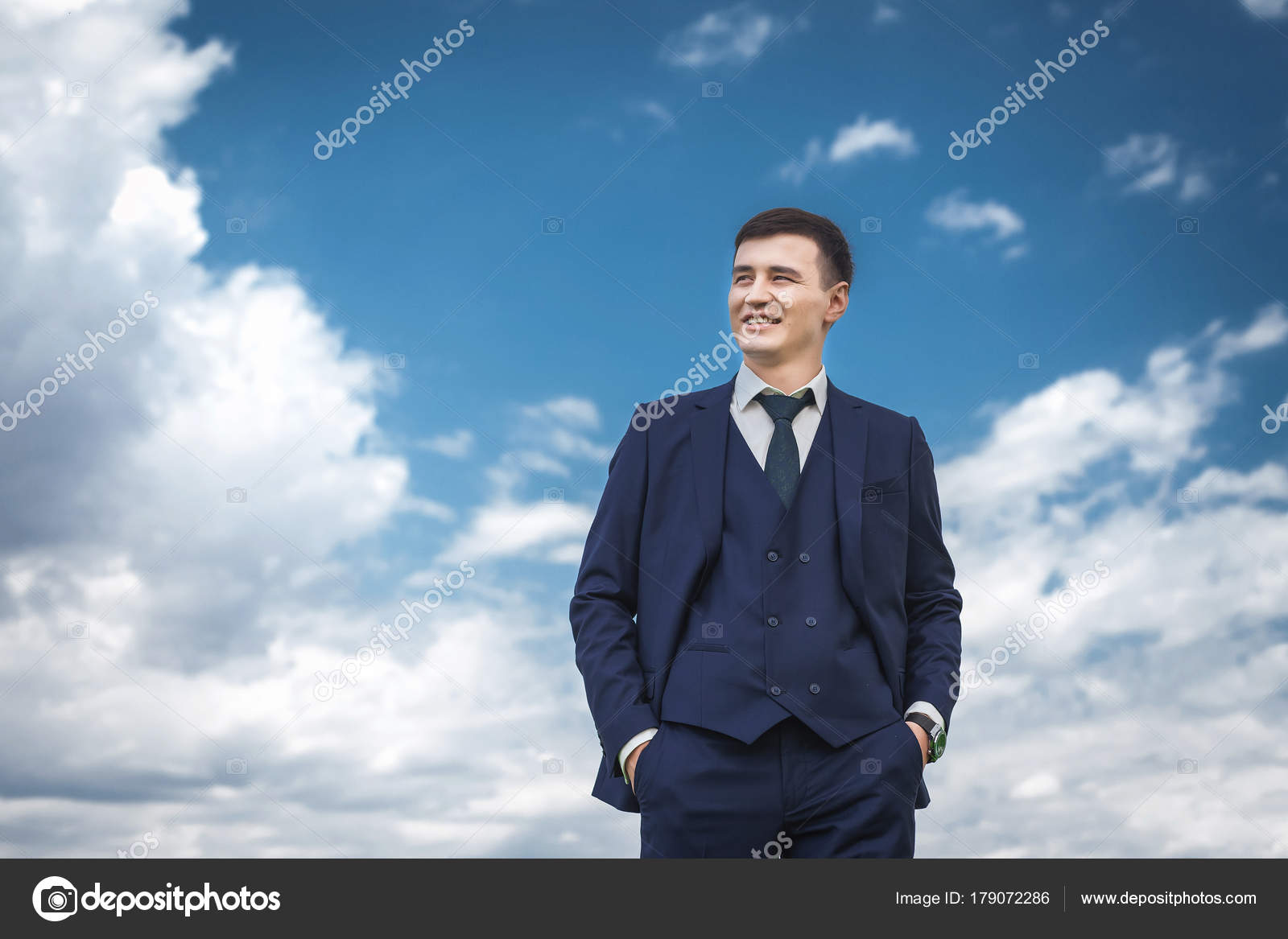 Handsome groom in a blue suit smiling against blue sky — Stock Photo ...