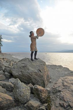 Evenki woman at sunset with a tambourine encourages spirits
