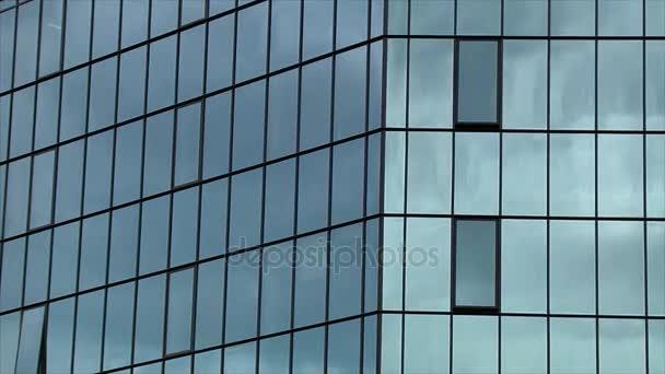 Temné mraky se odrážejí v oknech budovy úřadu. Časová prodleva.