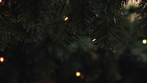 Lampy na umělý tmavě zelený smrk blikat. Silvestrovské a Vánoční pozadí. LED girlandy, zimní výzdoba.