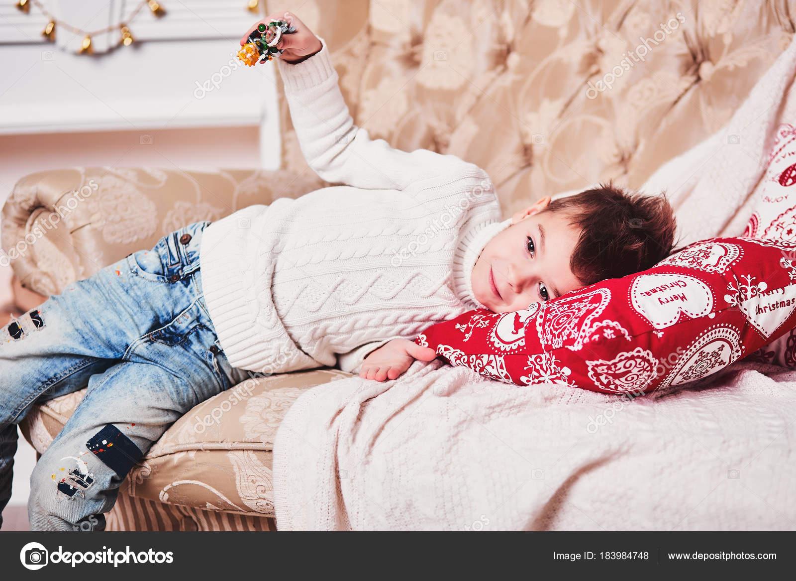 Niedlicher kleine Junge liegt auf dem Sofa mit einem Geschenk in ...