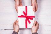 Férfi és női kezek cseréje egy ajándék csomagolva üres keret-ért, már több mint egy fából készült háttér