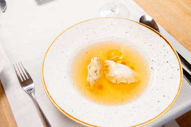 Dumplings in broth with an egg yolk served in a restaurant