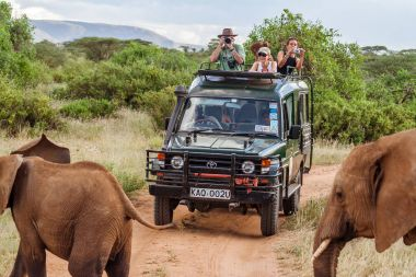 Masai Mara, Kenya, May 19, 2017: Tourists in an all-terrain vehicle exploring the African savannah on safari game drive stock vector
