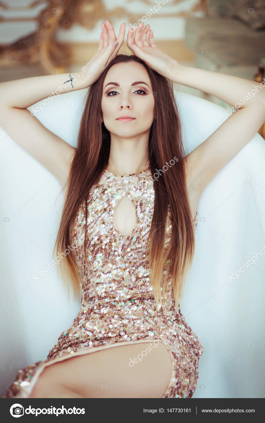 5a92524834 Beautiful stunning young woman in amazing glitter sequins dress lies in a  white bath. Bright full lips