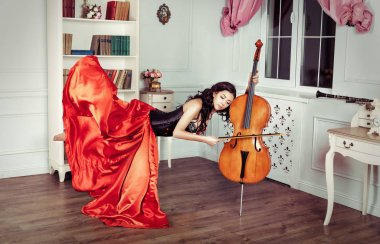 Beauty in mid-air. Full length studio shot of attractive young woman in orange dress hovering in air and playing the cello
