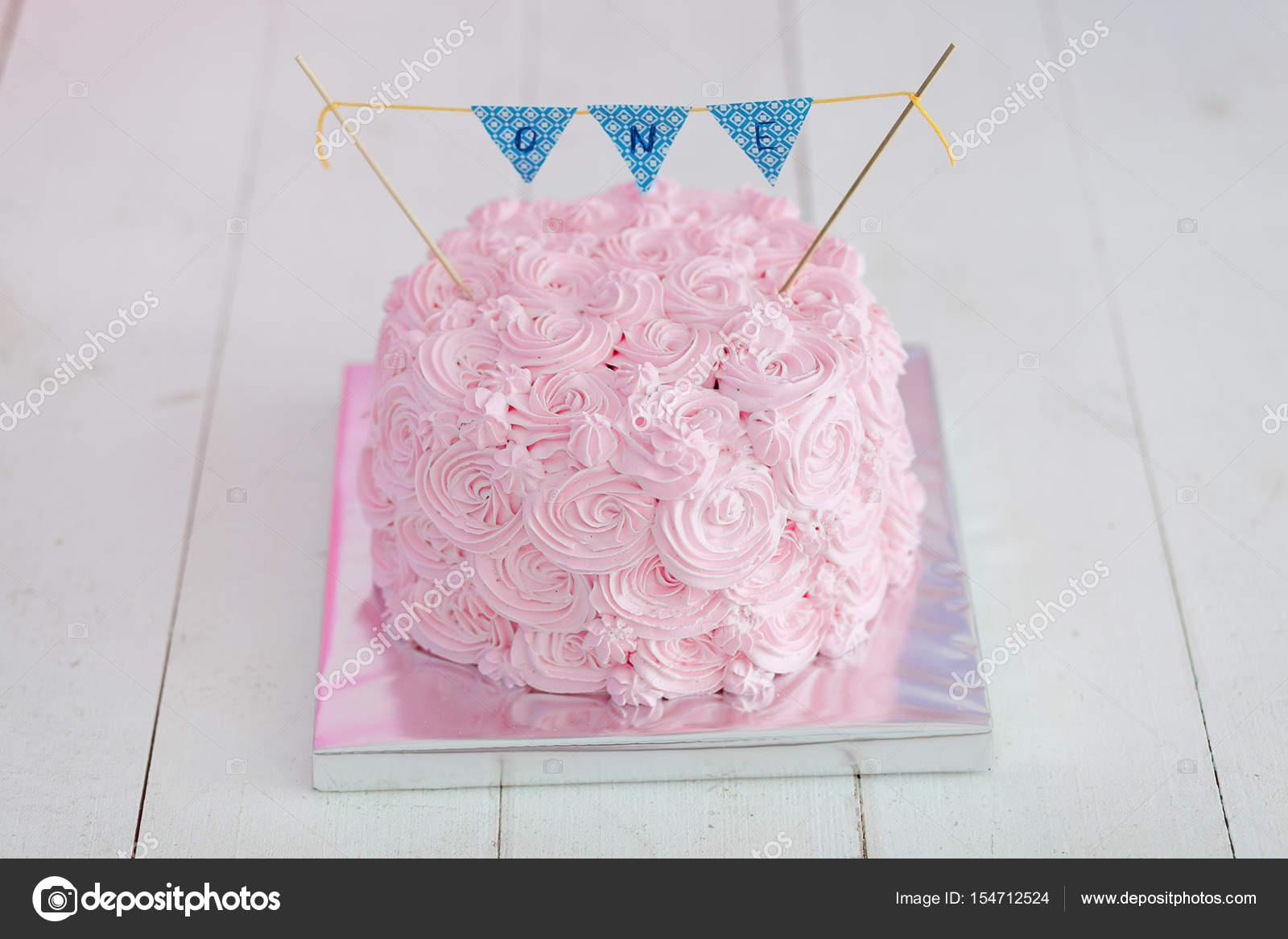 primer cumpleaños romper el pastel. Un pastel Rosa está sobre un ...