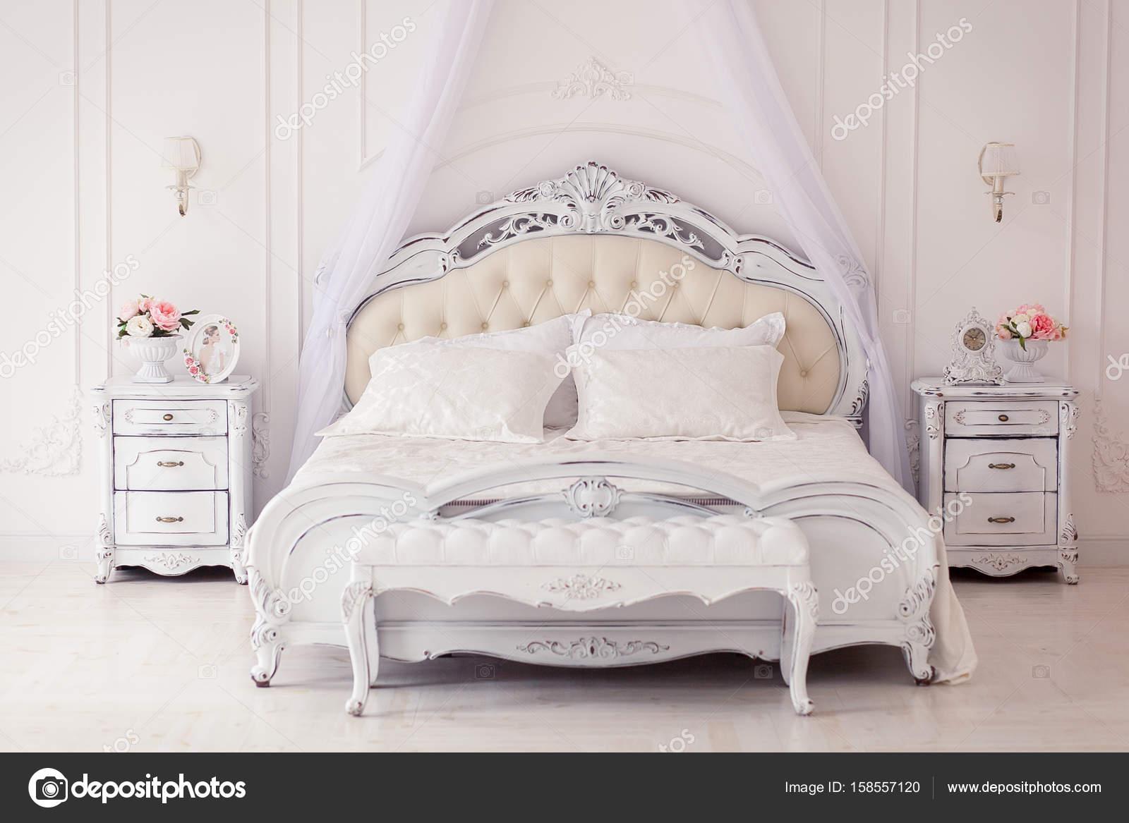 Luxe slaapkamer in lichte kleuren met gouden meubels details. Grote ...
