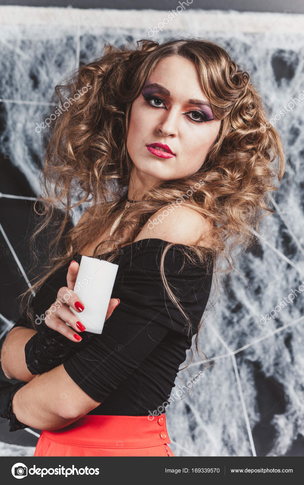a7391d9ab5 Girl the witch in front of black wall in a blouse and red skirt for  Halloween